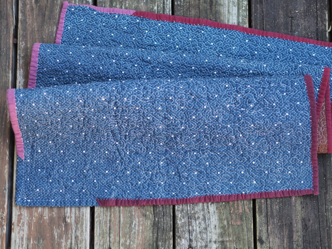back of baby quilt - navy blue fabric with various-sized white polka dots