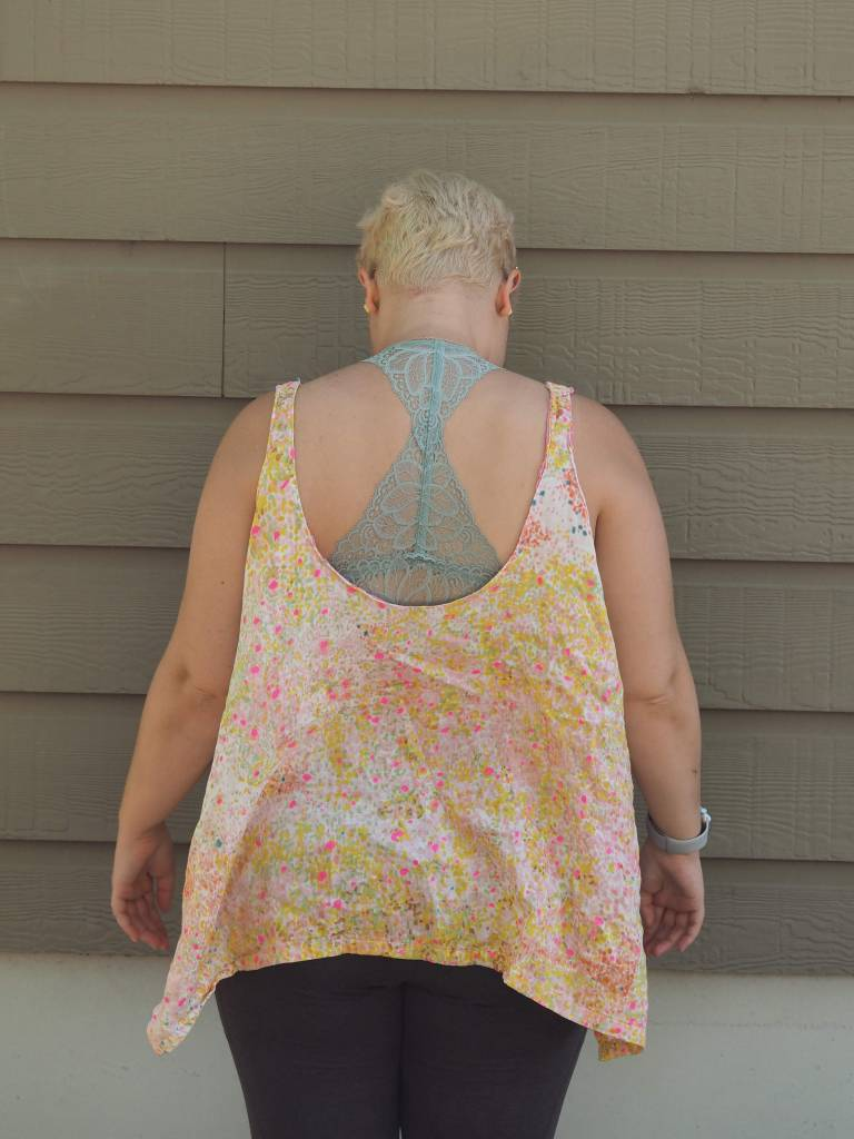 a white woman in a blue lacy bra and a white woven tank top with pale yellow and neon pink dots on it with her back to the camera
