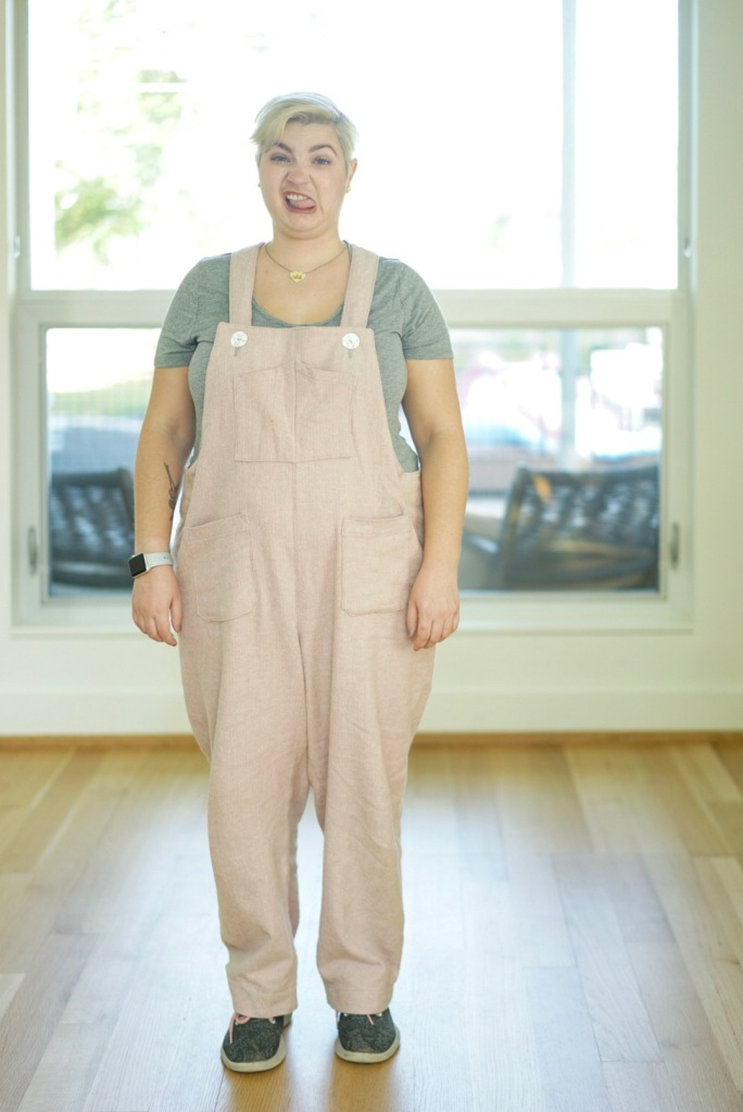 white woman indoors wearing pink overalls making a silly face