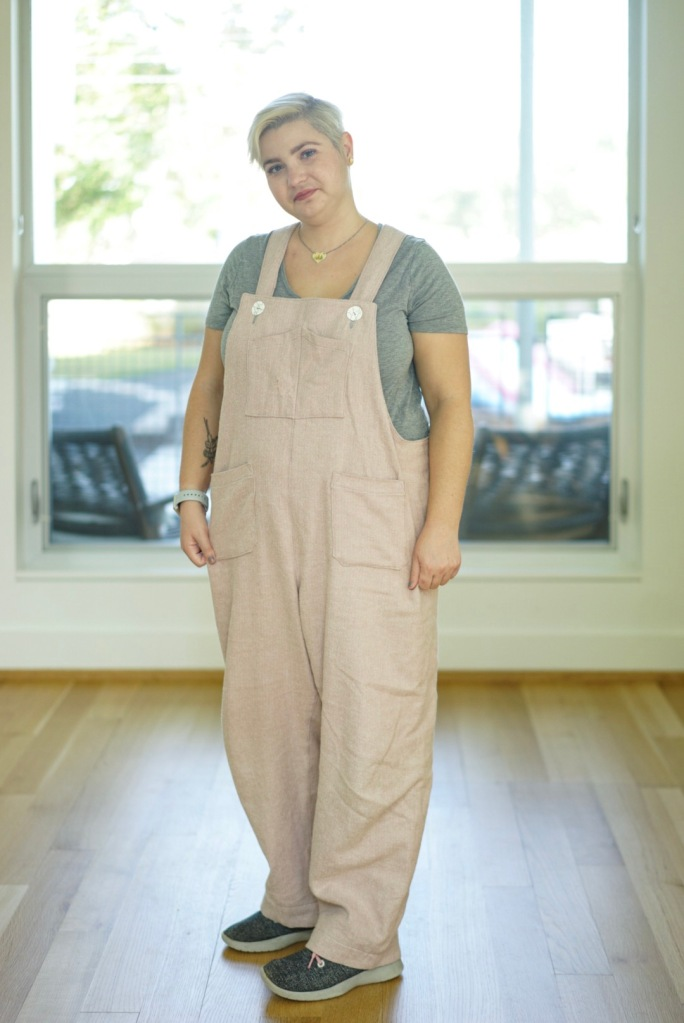 white woman indoors in pink overalls