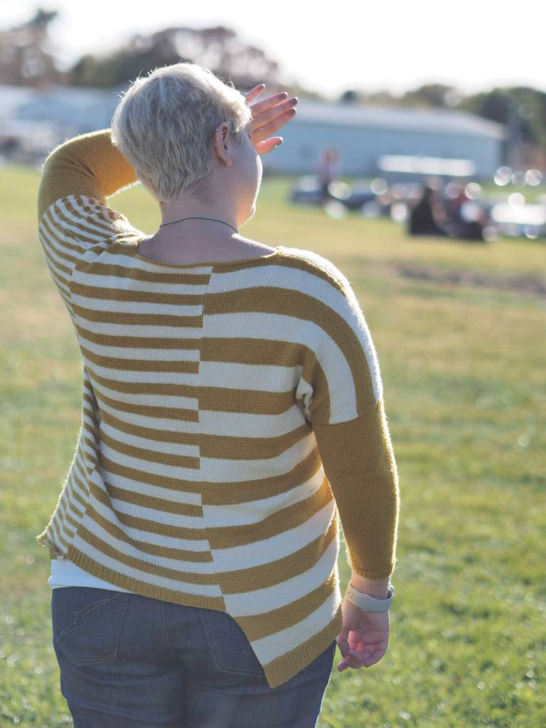 a woman in a yellow and white striped sweater stands in a field with her back to the camera, one arm blocking the sun from her eyes