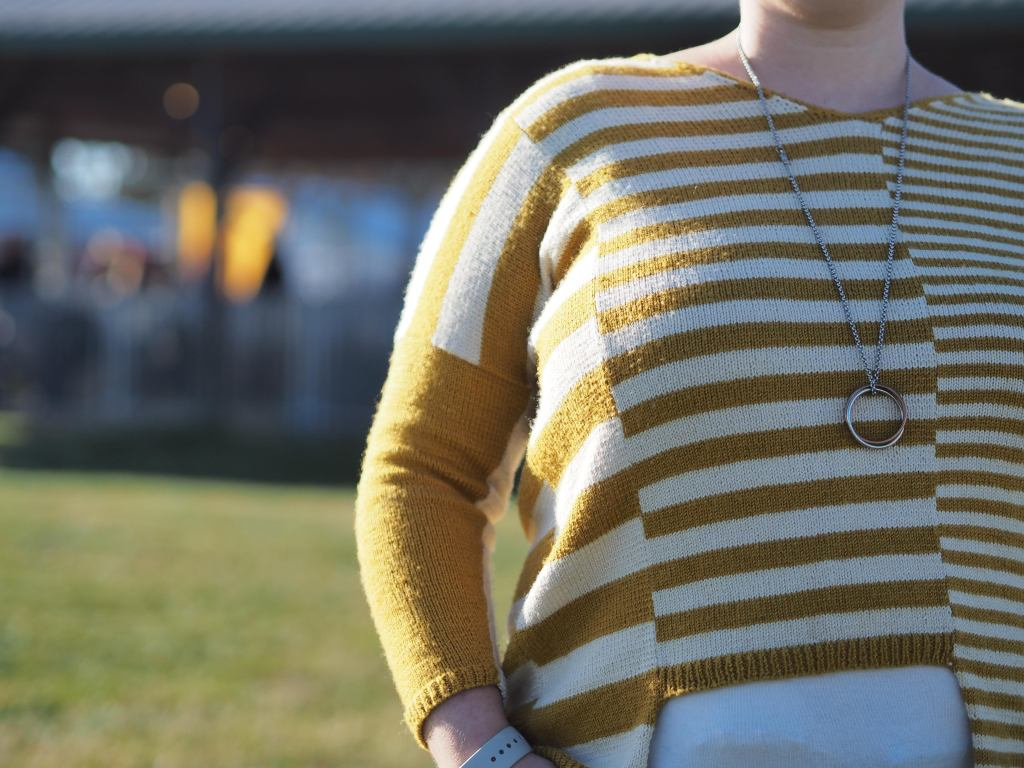 close up of the yellow striped sweater, showing half the front torso and an arm akimbo