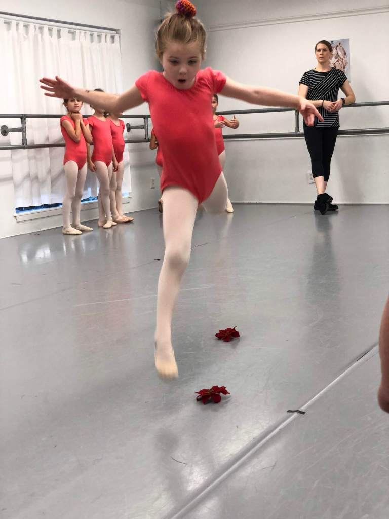 a young ballerina in a coral leotard jumping in a leap