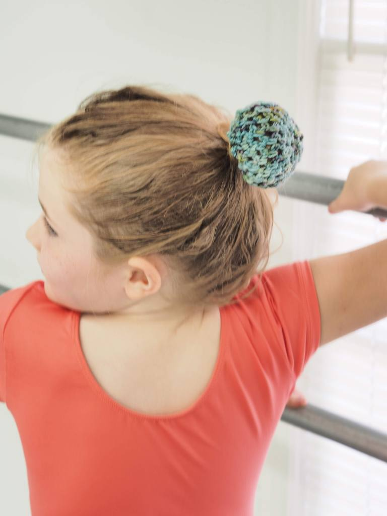 the profile of a ballerina with a blue bun cover on her hair