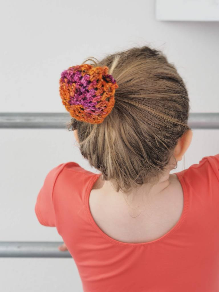 the back of a ballerina with a pink/orange bun cover