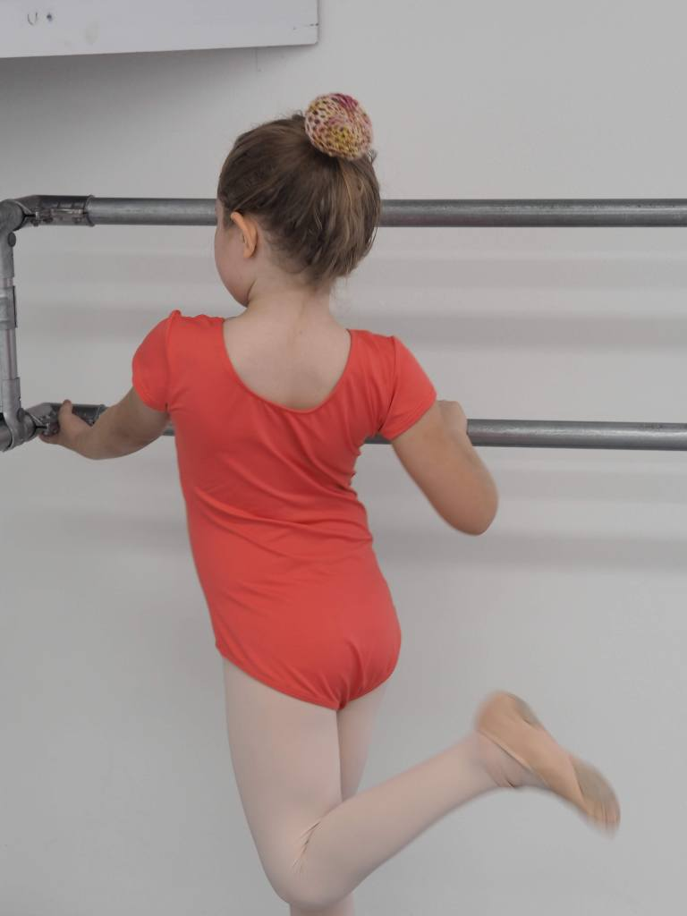 back view of  ballerina with a pink bun cover and one leg bent at the knee with foot behind her