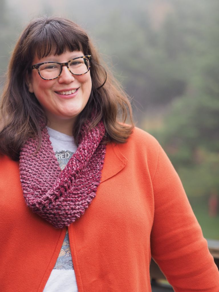 a white woman in an orange cardigan wear a pink and red cowl