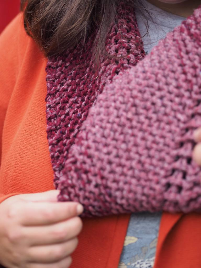 close up of pink and red cowl with woman's hand