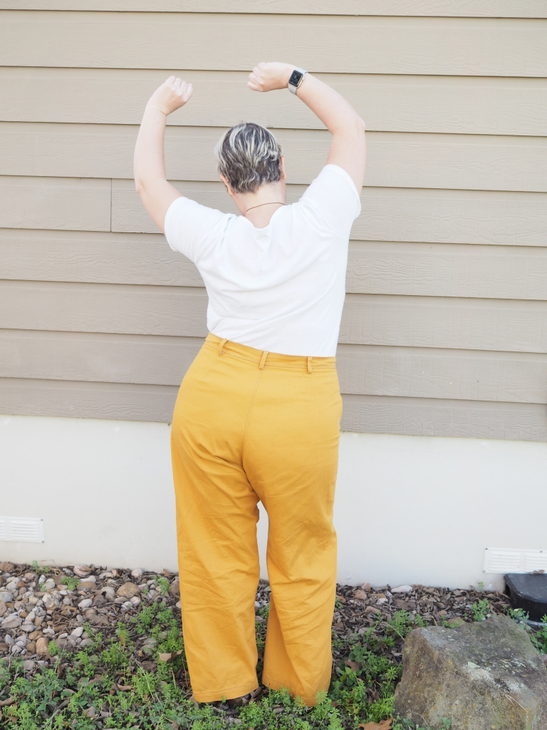 a white woman in mustard pants and a white tshirt with her back to the camera. her arms are above her head and her hip is cocked as is she was caught dancing.