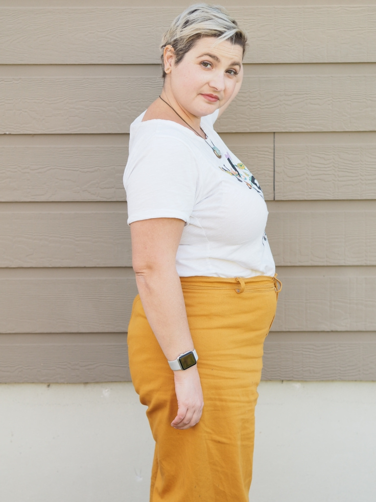 a white woman in yellow pants and a white tshirt. she is standing sideways looking at the camera with her back hand in her hair.