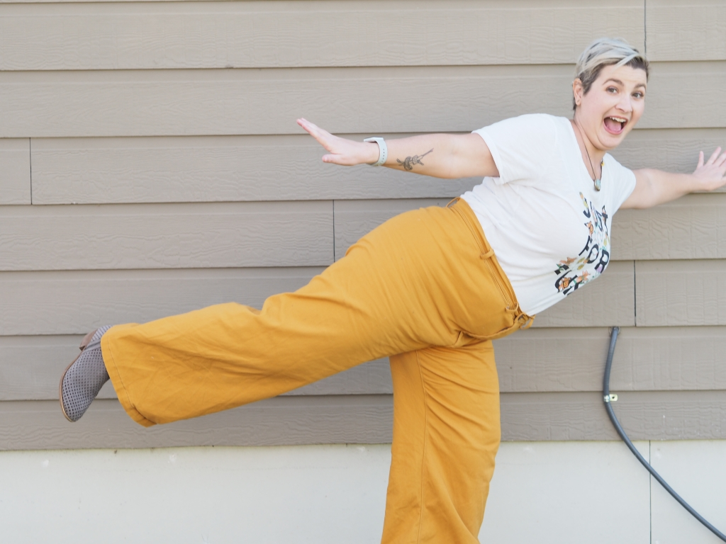 a white woman in mustard pants and a white shirt stands on one leg with the other behind her and her hands out, open-mouthed smiling at the camera