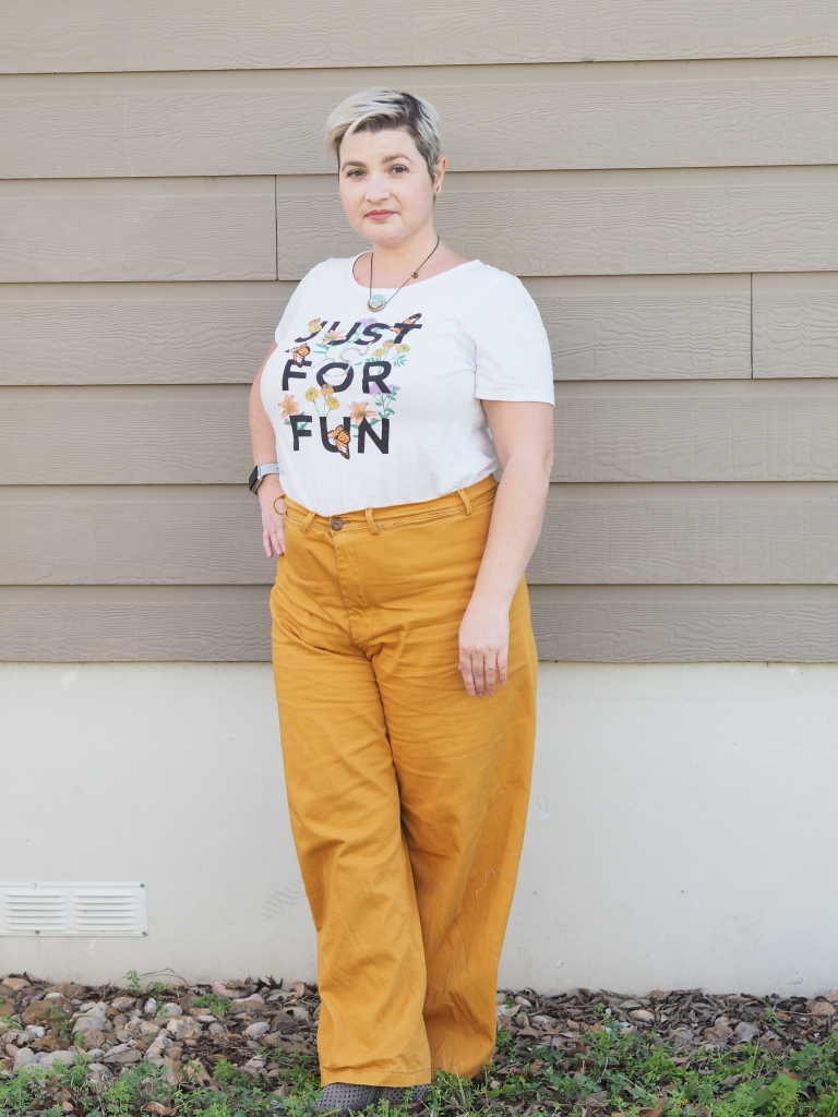 "a white woman in mustard pants and a white tshirt that says ""just for fun"" with flowers among the letters stands with legs crossed and a hand on her hip"