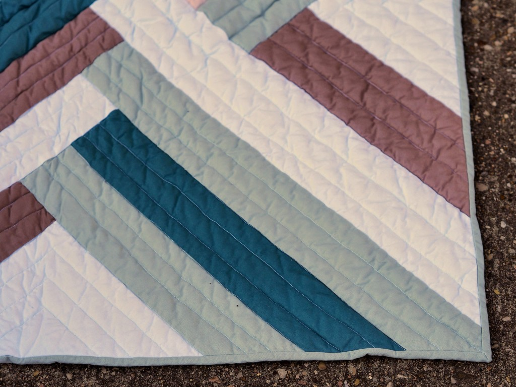 close up of a corner of a quilt on concrete. it shows the quilting on the front - straight lines across the strips of fabric that appear interwoven.