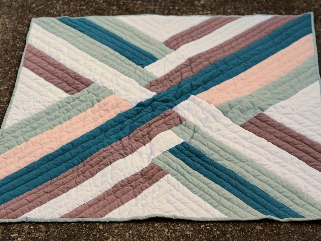 another view of the whole quilt top on concrete.