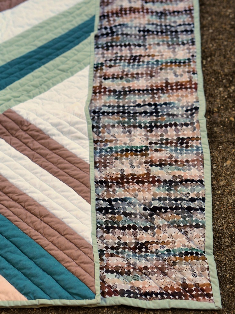 close up of a corner of a quilt on concrete. the quilt is folded over so the front and back are both visible. front has strips that look overlapping and woven, back has dots right next to each other that look like water colors. both in green, brown, and white colors.