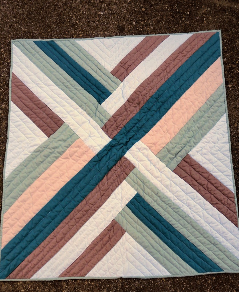 a quilt laying on concrete. the quilt has overlapping lines that look woven in white, browns, and greens.