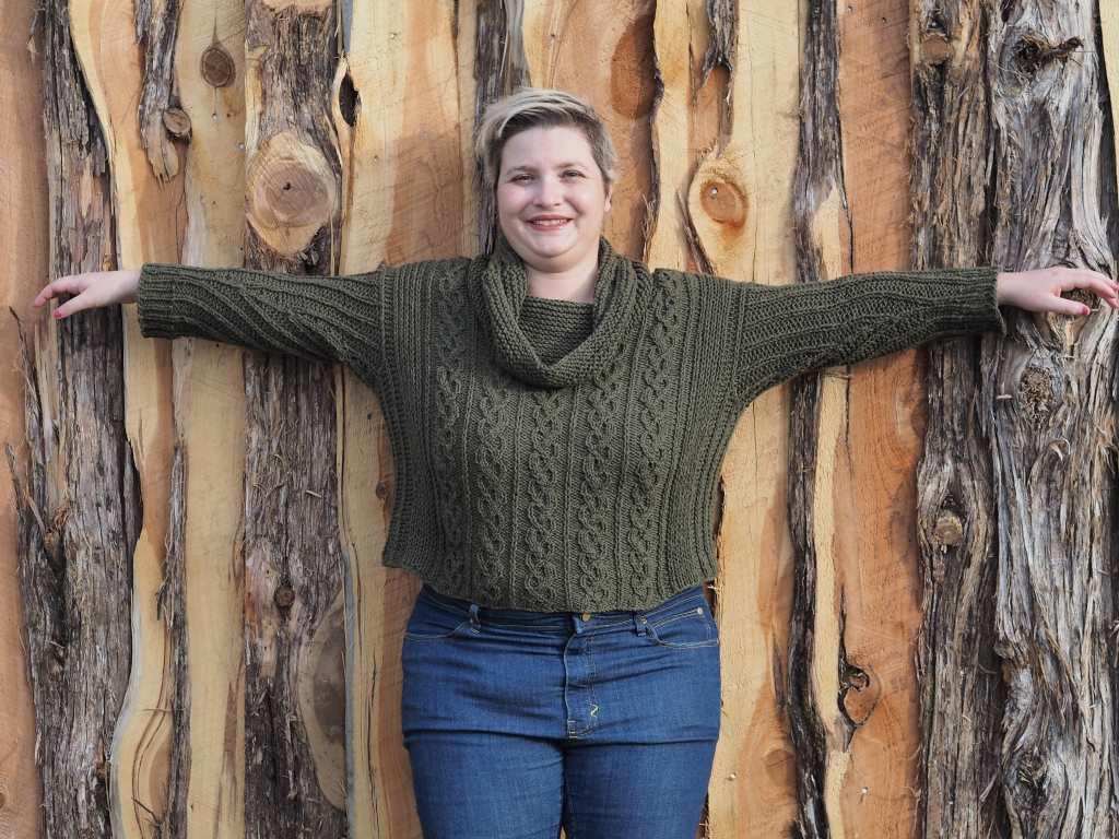 white woman in green cabled sweater and jeans stands in front of wooden fence, facing the camera with her arms up and out in a tee position.