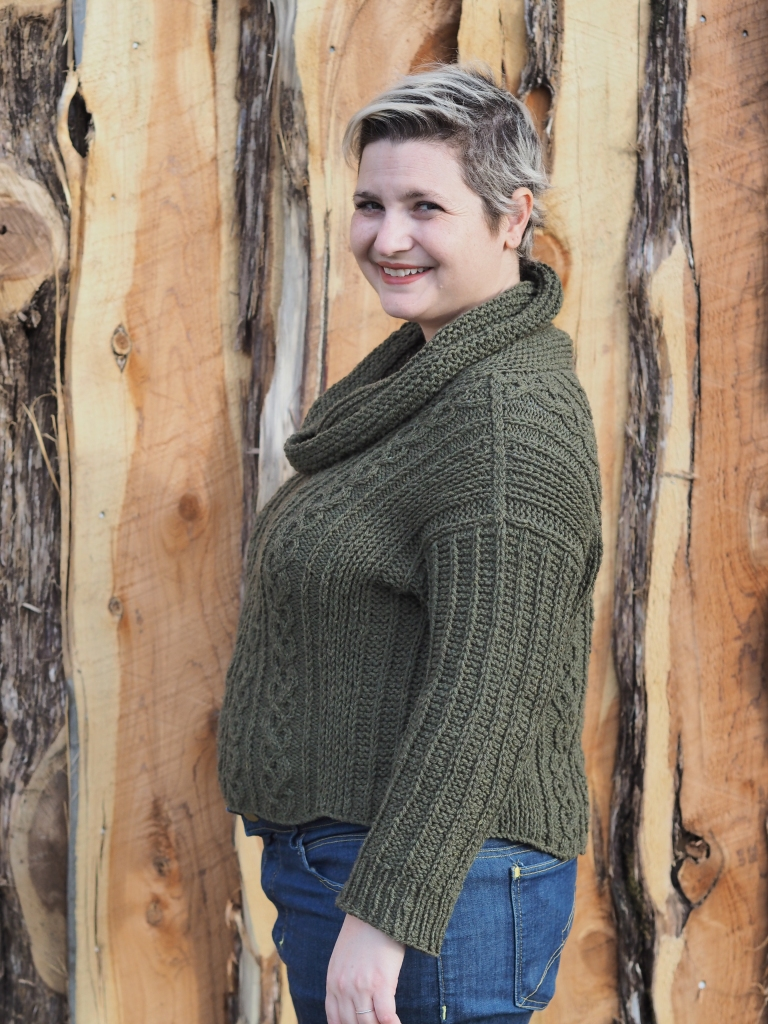 white woman in green cabled sweater and jeans stands in front of wooden fence, her body sideways and face turned to smile at the camera.