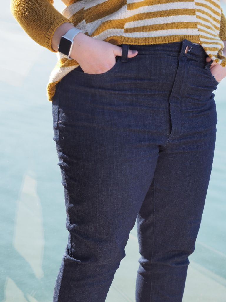 the bottom half of a woman. she is wearing jeans and you can just see the top of her sweater.