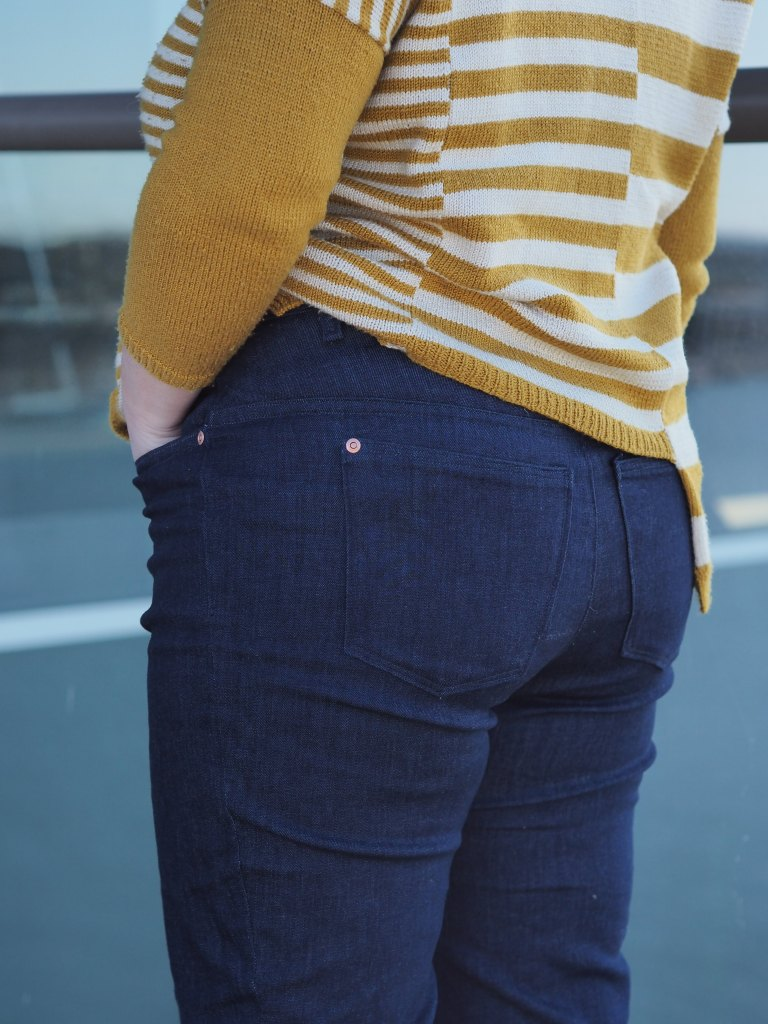 shoulders down of a woman at a 3/4 angle with her back to the camera. she is wearing a striped sweater and jeans with a hand in the pocket.