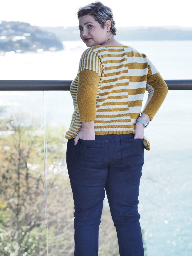 white woman stands with her back to the camera and face turned towards it. she is wearing a yellow and white striped sweater and has her hands in her back pockets.