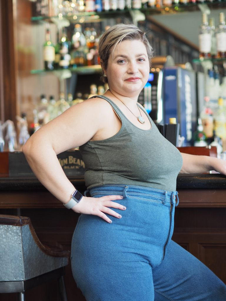 a white woman stands at a bar, her body sideways to the camera. she is wearing a tank top and jeans.
