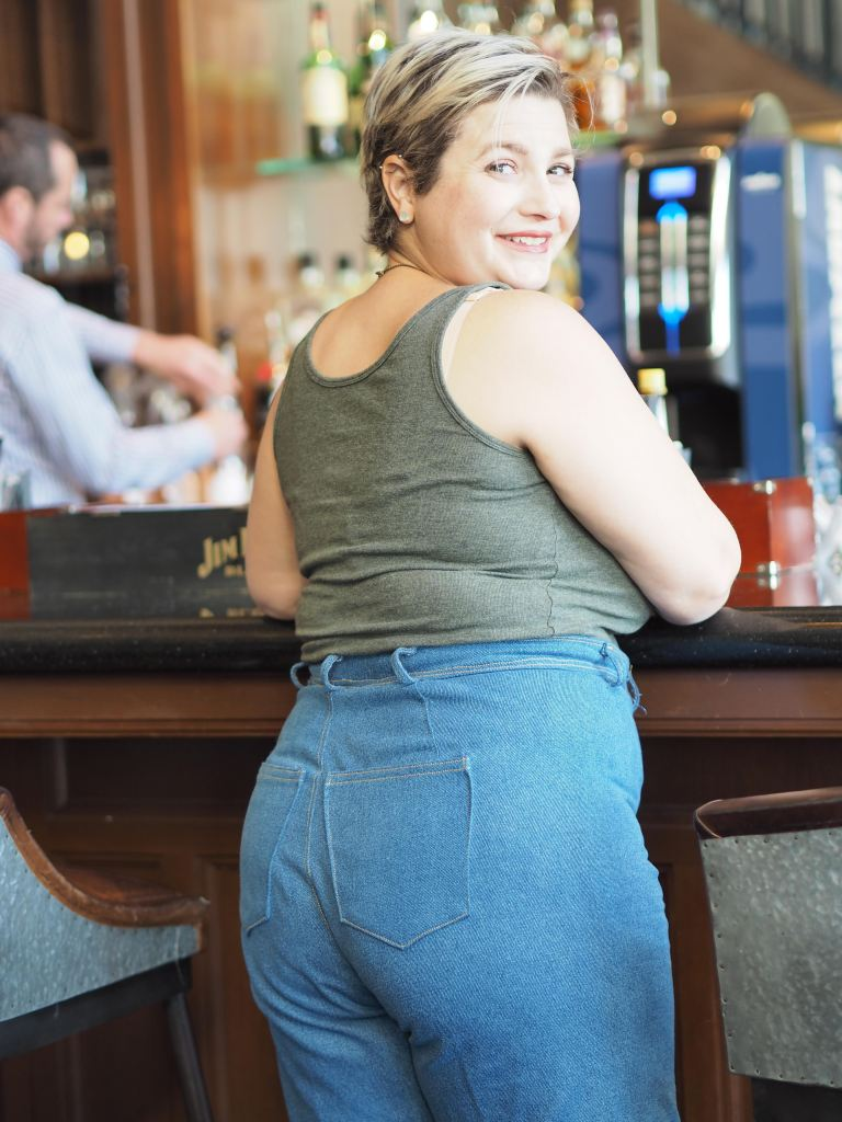 a white woman stands at a bar, her body facing away from the camera and head turned to smile at it. she is wearing a tank top and jeans.