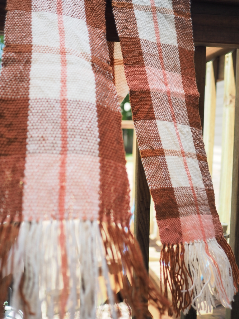 a plaid scarf in white browns and pink hangs over a wooden railing, billowing out in a breeze