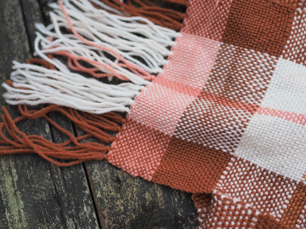 a plaid scarf in white, browns and pink laying on weather wooden planks