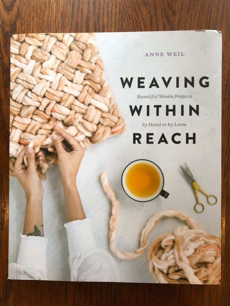 cover of the book weaving within reach. features a pair of hands tucking in strands of yarn on a project as well as a cup of tea, scissors, and a fluffy ball of yarn to create a cozy feel.