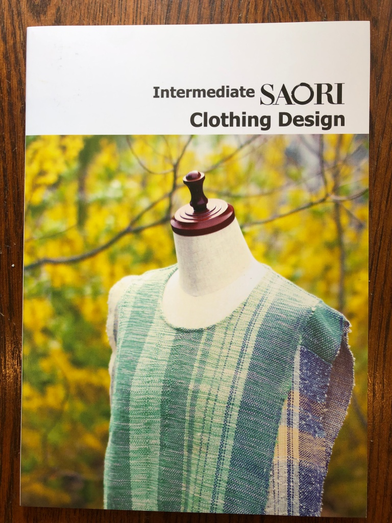cover of intermediate SAORI clothing design. it shows a shirt made of handwoven fabric with green stripes put on a dressform in front of a fuzzy wooded background.