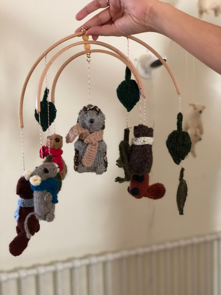 a hand holding a mobile of knitted animal toys and leaves against a white wall