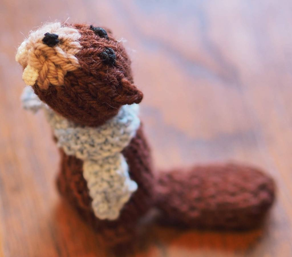 Close up on the head of a knitted beaver toy in a blue scarf